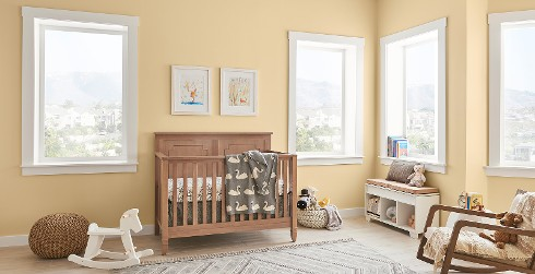 Youth room with yellow walls and white trim, wooden crib, casual style.