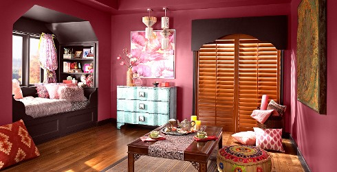 Eclectic styled youth room with deep red walls, black trim, and global themed decoration.