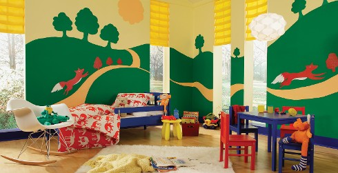 Inviting and friendly styled youth room with light yellow and green walls, blue on the trim, blue toddler bed, and painted hills with orange fox.