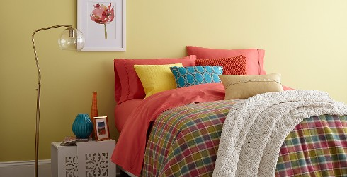 Inviting and friendly styled youth room with light yellow walls, white on the trim, and colorful bed spread.