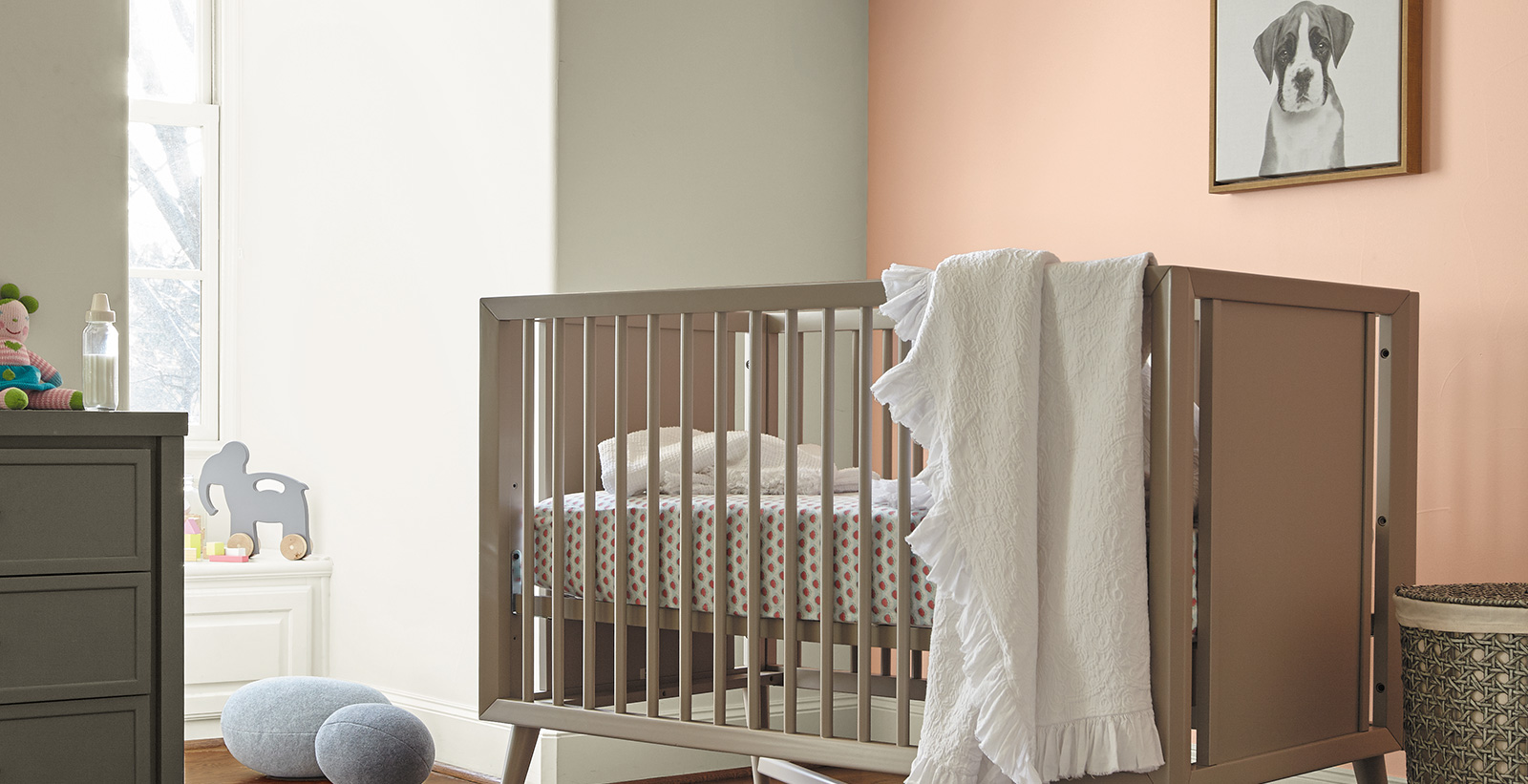 Inviting and friendly styled nursery youth room with white and light orange walls, white on the trim, and brown crib.