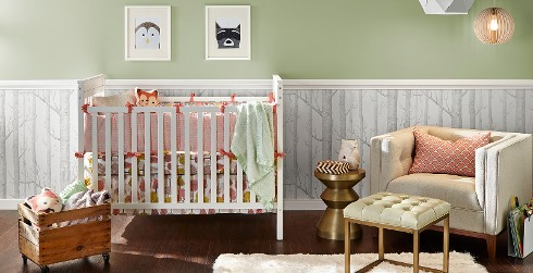 Modern styled youth nursery room with light green walls, white trim, and woodsy themed decoration.