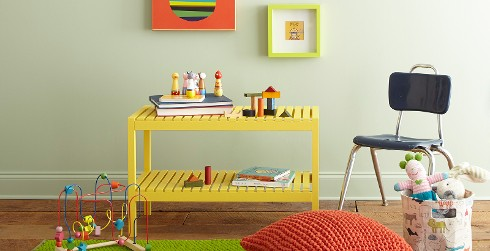Playroom with pale green walls, bright yellow child's table, surrounded by toys.