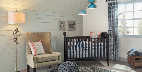 Versatile styled youth room with white and light green walls, light blue on the trim, stuffed animals, and a wooden crib.