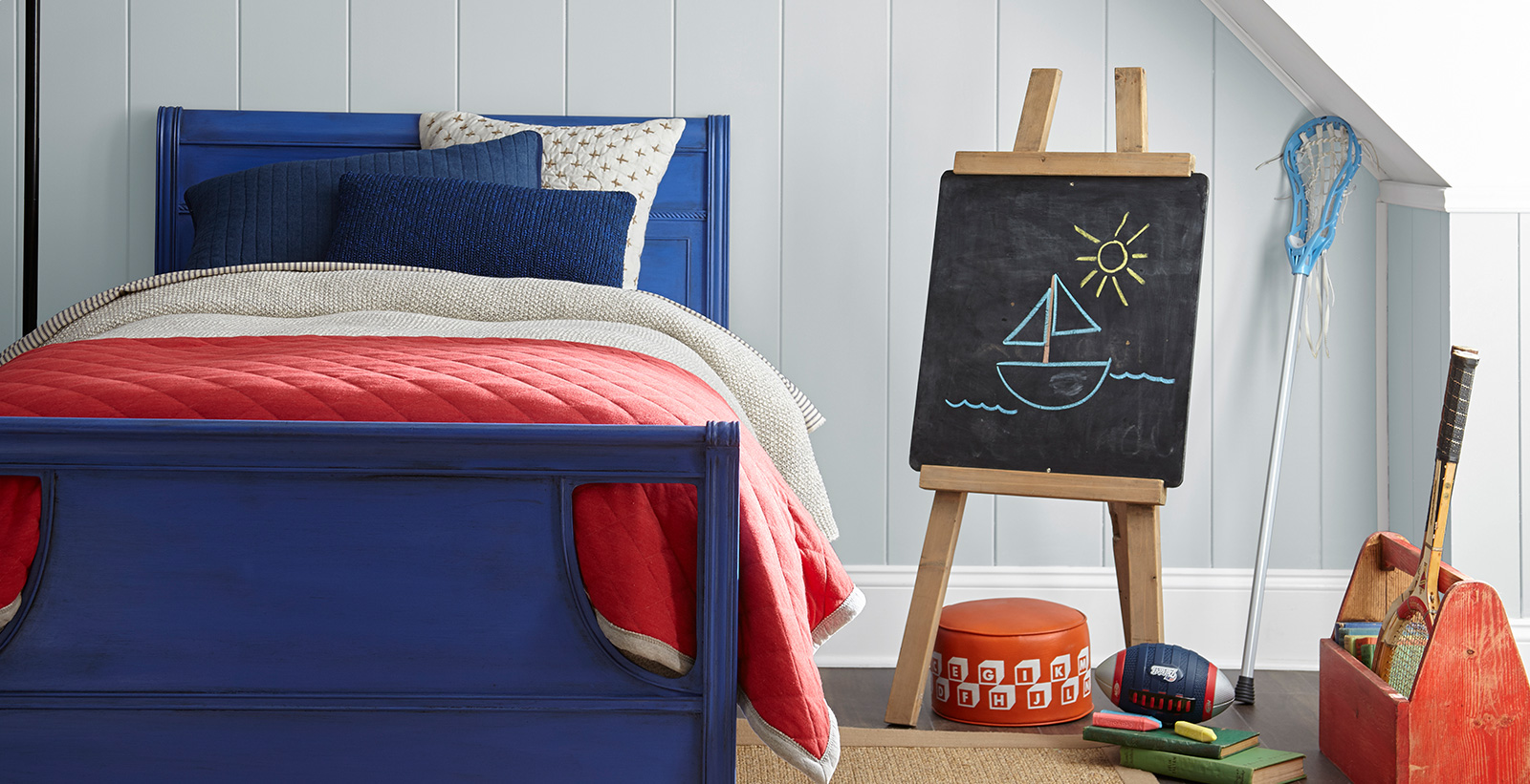 Coastal styled youth room with light gray walls, white trim, dark blue chalk paint styled bed with a chalkboard and sports equipment.