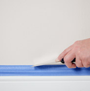 Person using a putty knife to press down painter's tape on a wall