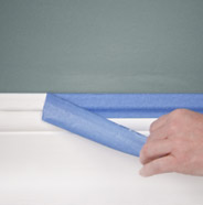 Person removing painter's tape from a painted wall