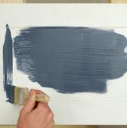 Persona pintando la puerta de un gabinete