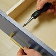 Persona usando un destornillador para reinstalar los accesorios de un cajón del gabinete