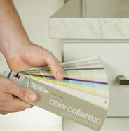 Persona eligiendo un color de pintura de un muestrario de Behr
