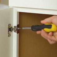 Persona utilizando un destornillador para quitar la puerta de un gabinete