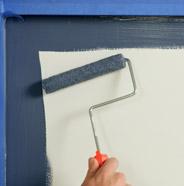 Persona pintando los paneles del gabinete con un rodillo