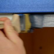 Persona pintando la parte superior del marco de un gabinete con una brocha