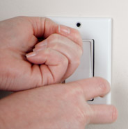 Person removing cover plates from light switches and outlets