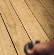 Persona rociando una terraza de madera con una manguera