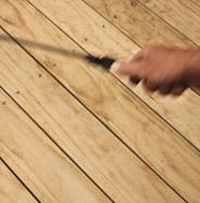 Persona usando un rociador de bomba en la terraza de madera