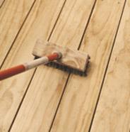 Restregar la terraza de madera con un cepillo de cerdas duras