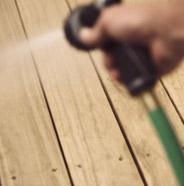 Persona enjuagando una terraza de madera con una manguera