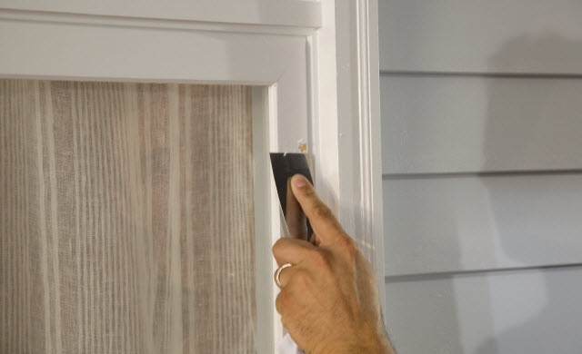 Image demonstrating a person using a tool to peel paint off of a window frame.