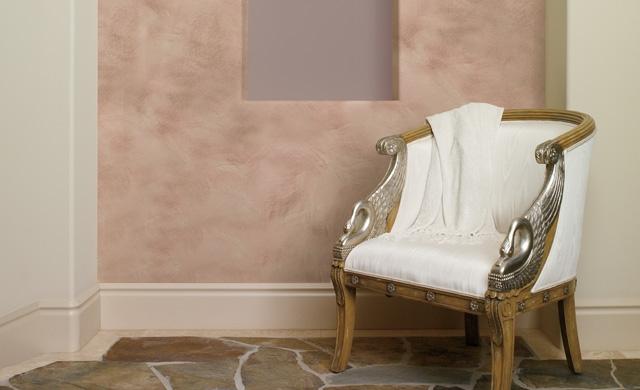 Silla clásica frente a una pared con acabado efecto lavado de color pintada en blanco y rosa