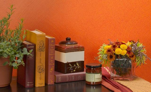 Objetos de decoración sobre una mesa al lado de una pared pintada en color anaranjado