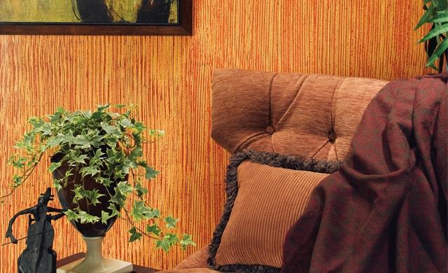 Parte superior de un sillón frente a una pared con acabado de líneas rectas en color anaranjado