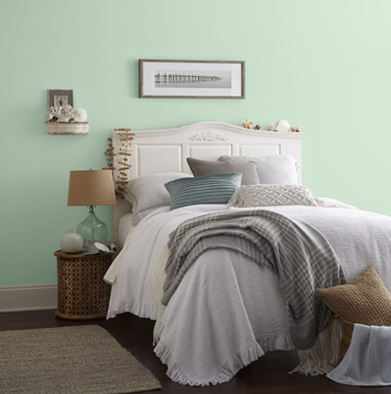 Full sized bed with white headboard placed against green wall