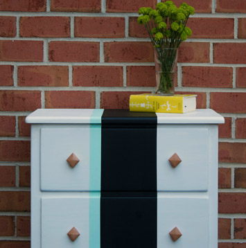 Dresser in front of brick wall