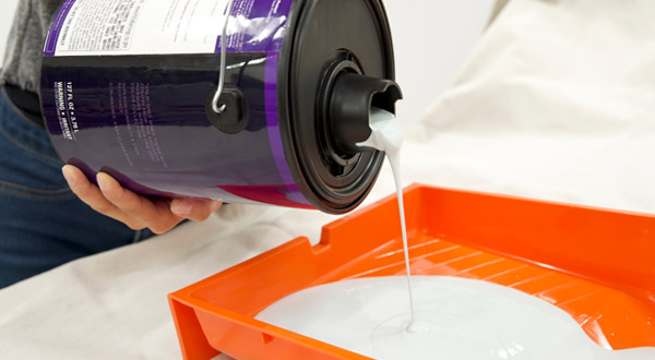 Close up of paint being poured into tray using Simple Pour Lid.