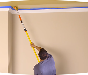 A man painting a ceiling with extension roller