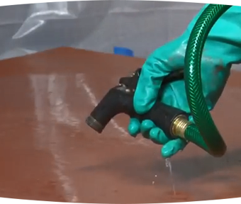 A person's hand wearing a rubber glove spraying water out of hose onto the ground