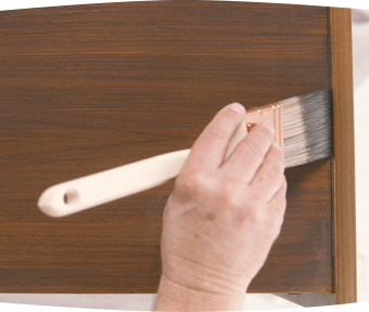 A person staining an end table with a paint brush