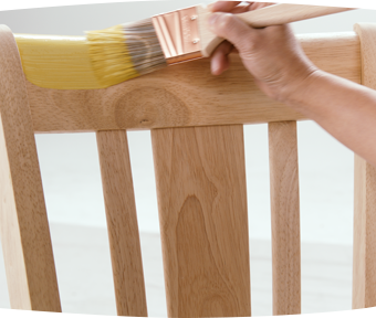 A person painting a wooden chair with a paint brush