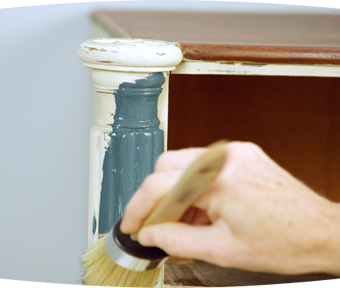 Person painting detailed areas of a dresser with a paint brush