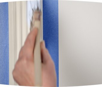 Person using a paint brush to paint trim
