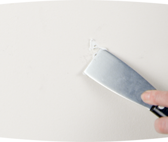 Person using a putty knife to fill a hole with spackle
