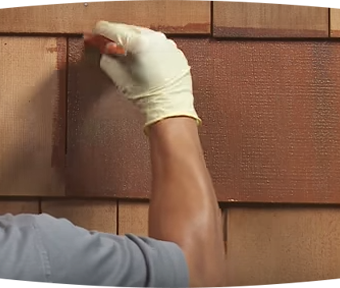 Person staining wood siding with paint brush
