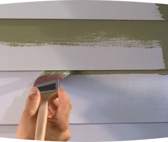 Person painting an olive green color onto a white house