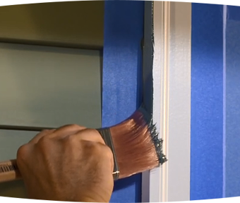 Person painting trim of a house with blue tape around it