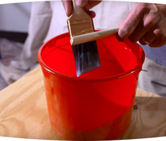Person cleaning off a paint brush over a red bucket