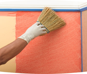 Person applying paint to a wall with a large paint brush