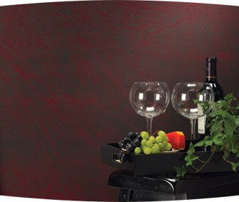 A bottle of wine, two glasses, and fruit sitting on a table