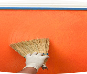 Person applying wavy lines of paint onto wall with a broom
