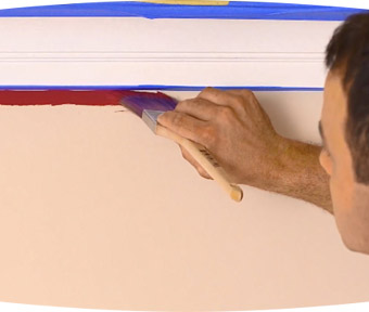 Person using a paint brush to paint under trim