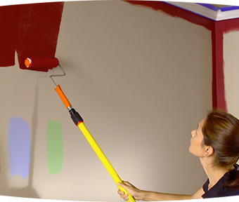 Person painting red paint with paint roller on a wall