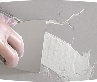 Person repairing cracked painted drywall