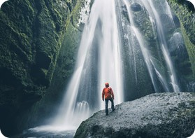 Lone hiker standing in front of majestic waterfall.