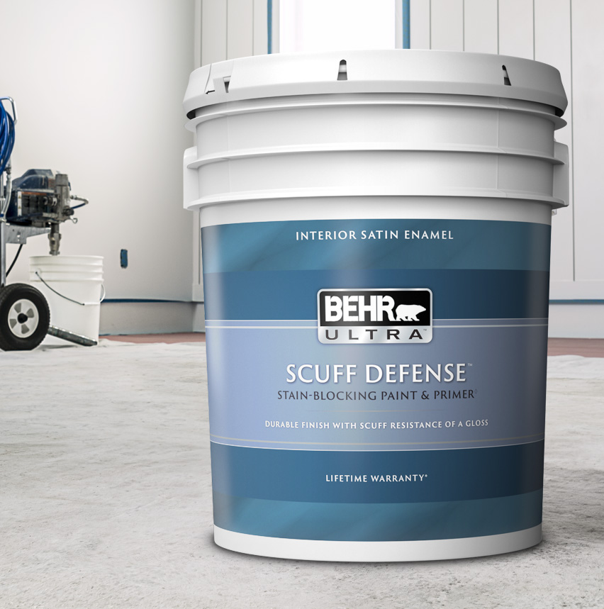 Pail of Behr Ultra paint in a room, paint sprayer in background.