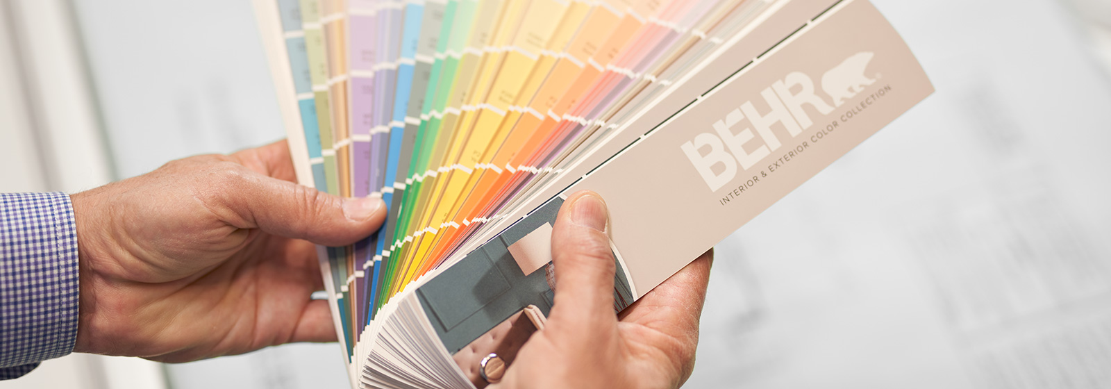 A large image of a BEHR Color Fan Deck held by a hand.