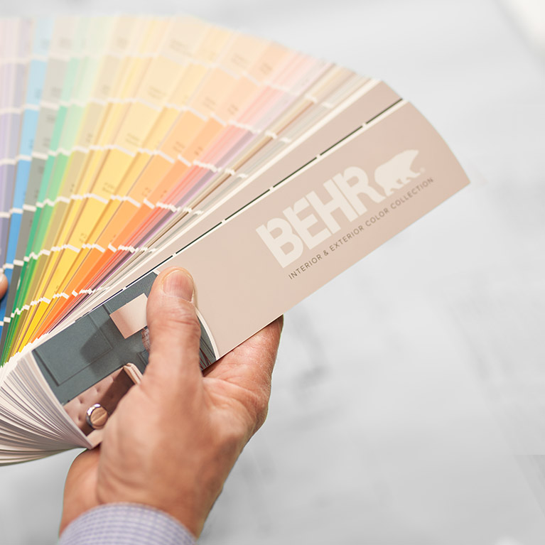 A small image of a BEHR Color Fan Deck held by a hand.
